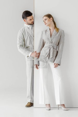 fashionable young man in vintage jacket touching his girlfriend from behind white wall