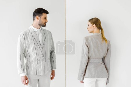 young male and female models in vintage clothes looking at each other isolated on white