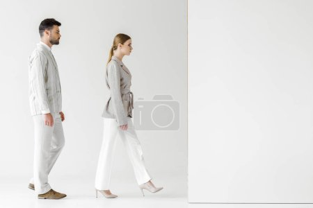 young male and female models in vintage clothes walking at white wall