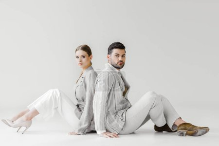 couple of stylish models in vintage clothes sitting on floor and leaning back to back on white