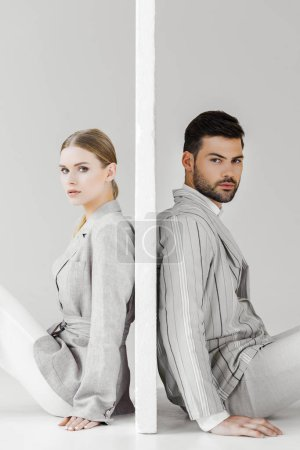 side view of couple of models in stylish jackets leaning back on sides of wall on white and looking at camera