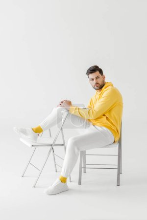 attractive young man in yellow hoodie sitting on chairs on white