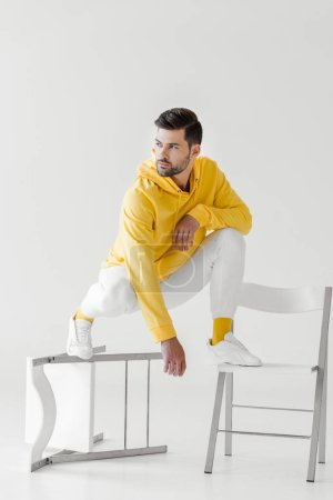stylish young man in yellow hoodie sitting squats on flipped chairs on white