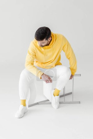 thoughtful young man in yellow hoodie sitting on flipped chair on white