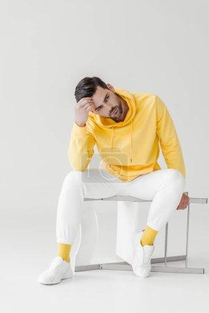 élégant jeune homme assis sur une chaise retournée sur blanc à capuche jaune