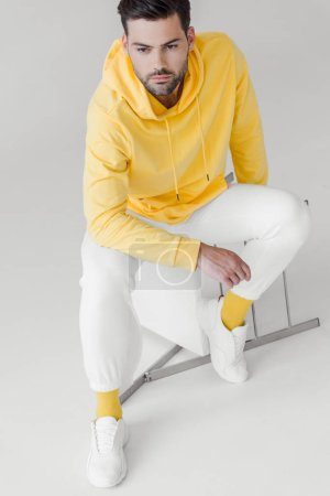 Photo for High angle view of handsome young man in yellow hoodie sitting on flipped chair on white - Royalty Free Image