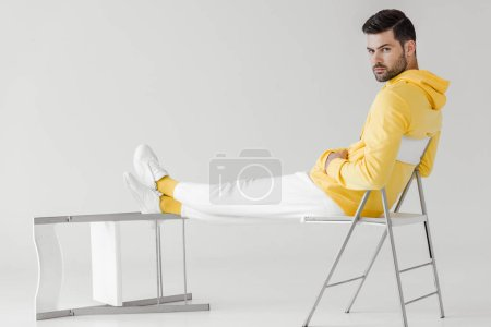 handsome young man in yellow hoodie sitting relaxed on white and looking at camera