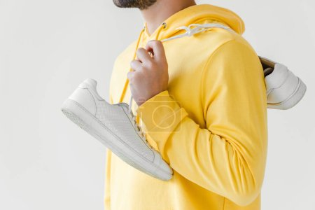 cropped shot of young man in yellow hoodie with white sneakers hanging on shoulder isolated on white