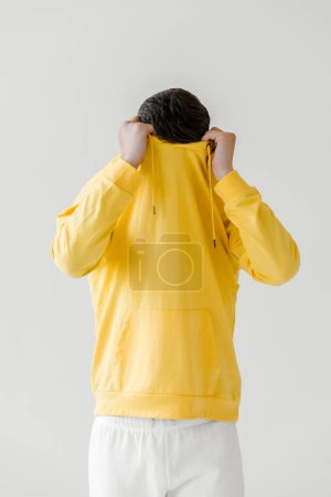 young man taking off yellow hoodie isolated on white