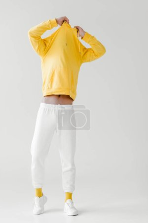 young man taking off yellow hoodie on white