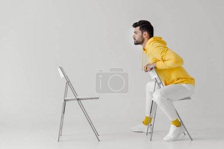 Foto de Elegante joven con capucha amarillo sentado en la silla frente a otra silla en blanco - Imagen libre de derechos