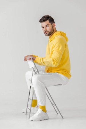 side view of handsome young man in yellow hoodie sitting on chair on white