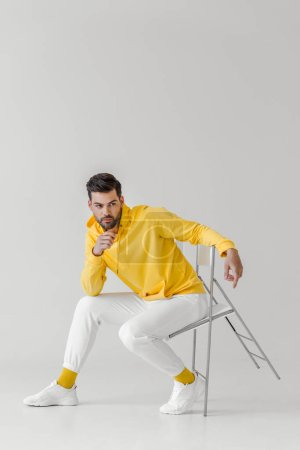 attractive young man in yellow hoodie sitting on chair on white