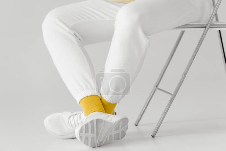 cropped shot of man in white pants and sneakers with yellow socks on white