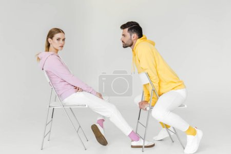 side view of young male and female models in pink and yellow hoodies sitting on chairs on white