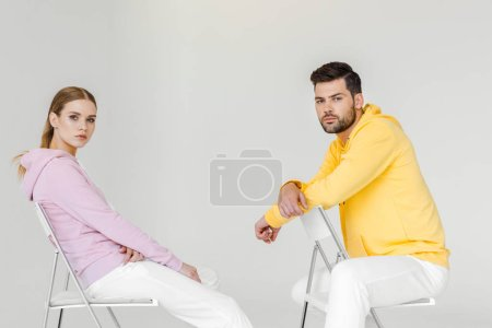 side view of young male and female models in pink and yellow hoodies sitting on chairs and looking at camera on white