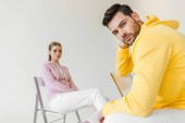 stylish young male and female models in pink and yellow hoodies sitting on chairs isolated on white