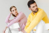young male and female models in pink and yellow hoodies sitting on chairs isolated on white