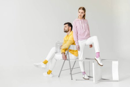 young male and female models in pink and yellow hoodies on white