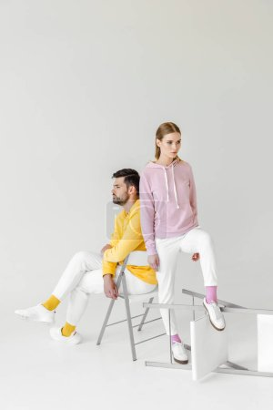 young male and female models in stylish hoodies on white