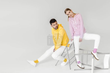 stylish young male and female models in colorful hoodies sitting on chairs on white