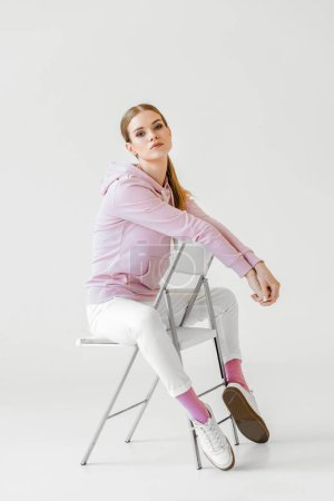 fashionable young woman in stylish hoodie sitting on chair on white and looking at camera