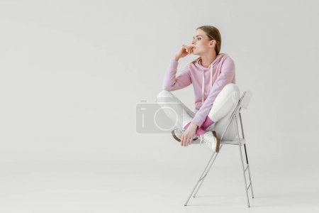 thoughtful young woman in pink hoodie sitting on chair on white and looking away