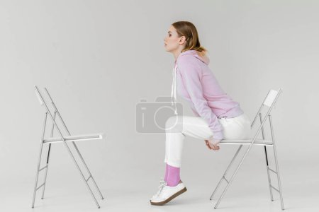 side view of stylish young woman sitting on chair in front of another empty chair on white