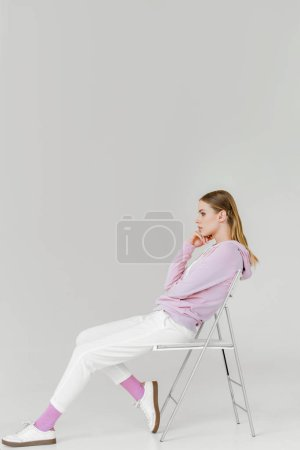 side view of stylish young woman sitting on chair on white