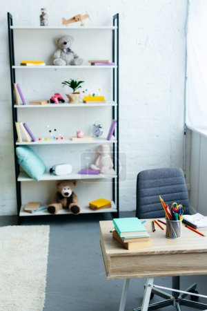 books and toys on shelves and wooden table with school supplies