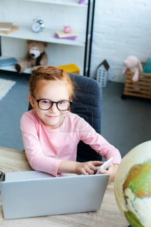 high angle view of adorable red haired schoolchild in eyeglasses smiling at camera while using smartphone and laptop