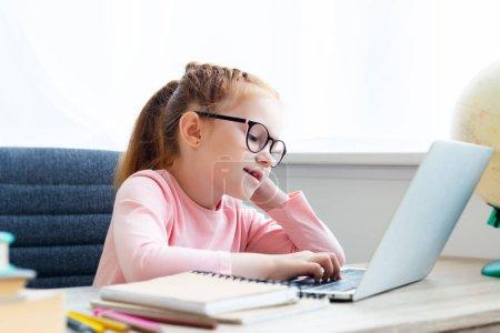 hermosa colegiala de lentes usando el portátil mientras está sentado en el escritorio
