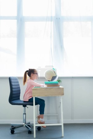 side view of little schoolgirl studying with books and laptop at home