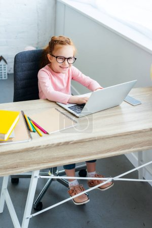 high angle view of beautiful kid in eyeglasses using laptop and smiling at camera