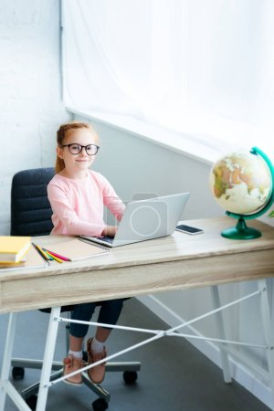 high angle view of child in eyeglasses smiling at camera while using laptop and studying at home