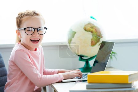adorable happy schoolchild in eyeglasses studying with laptop and books at home
