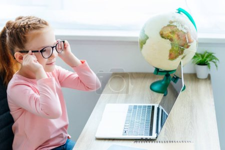 cute smiling child using laptop while sitting at desk