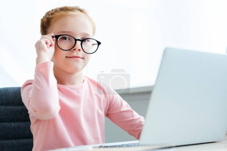 beautiful schoolchild adjusting eyeglasses and smiling at camera while using laptop
