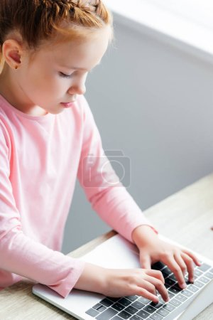 Photo for High angle view of beautiful little schoolgirl using laptop - Royalty Free Image
