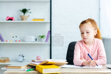 beautiful red haired schoolgirl sitting at desk and studying at home