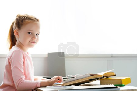 beautiful schoolgirl smiling at camera while studying at home