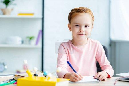 Photo pour Belle écolière rousse souriant à la caméra tout en écrivant dans un carnet au bureau - image libre de droit