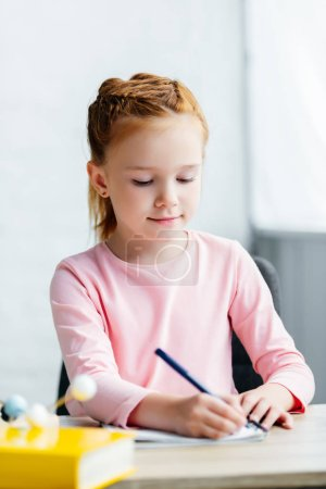 beautiful smiling schoolgirl sitting at desk and taking notes