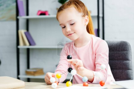 beautiful smiling redhead schoolgirl studying with molecular model at home