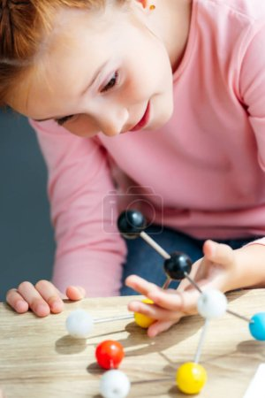 close-up view of cute smiling schoolgirl looking at molecular model