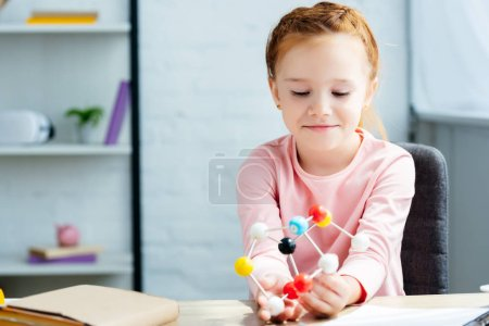 beautiful smiling schoolgirl sitting at desk and holding molecular model