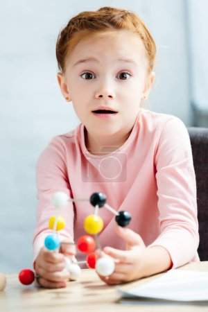 shocked child holding molecular model and looking at camera