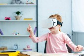 cute little schoolgirl using virtual reality headset at home