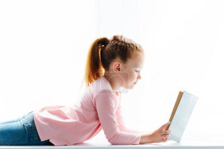 beautiful little schoolgirl lying on windowsill and reading book