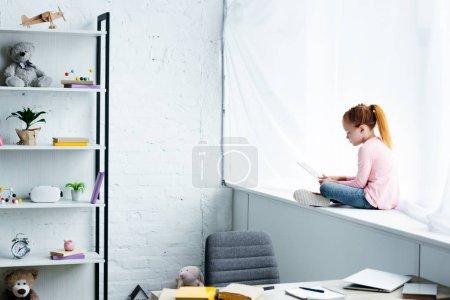 beautiful redhead schoolgirl using digital tablet while sitting on windowsill